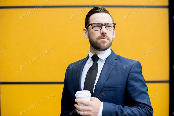 Handsome man holding cup of hot drink