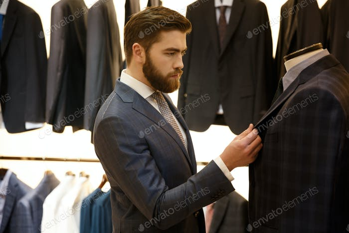 Side view of man choosing a jacket in shop