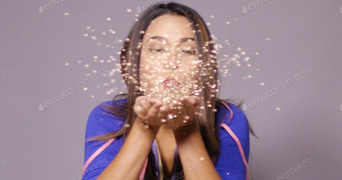 Fun young woman blowing a spray of confetti
