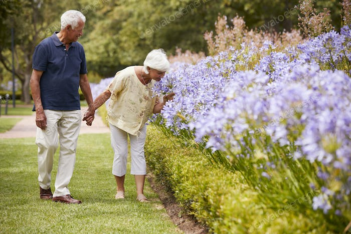 Senior Couple Holding Smelling Flowers On Walk In Park Together