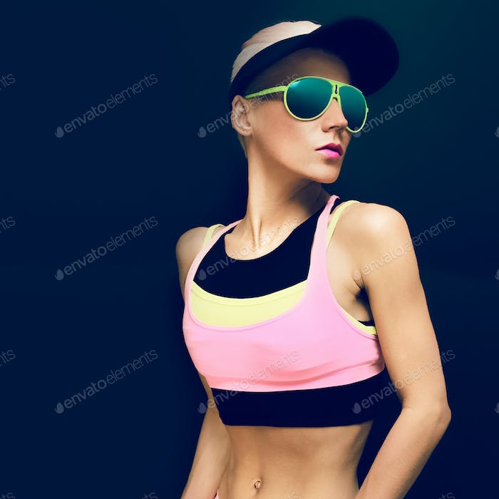 Fitness girl in bright trendy sport clothes on a black backgroun