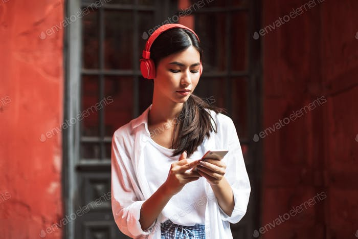 Young woman in white shirt and red headphones thoughtfully usina