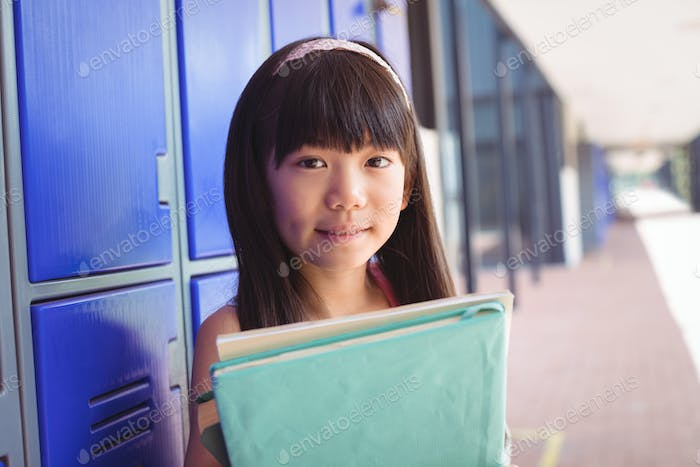 Portrait of elementary schoolgirl holding books in corridor
