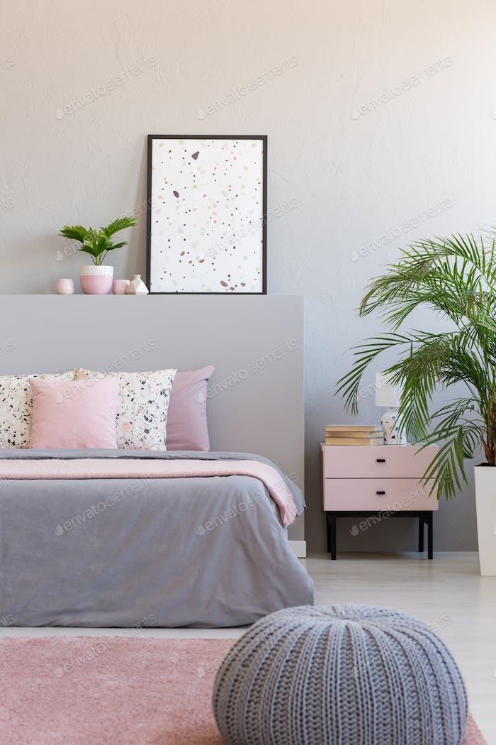 Grau Hocker neben Bett mit Kissen im modernen Schlafzimmer Interieur w