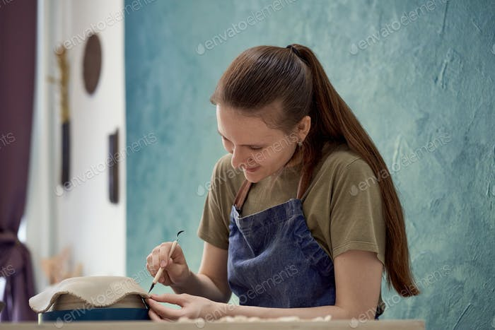Young girl making ceramic bowl in class. Creative hobby concept