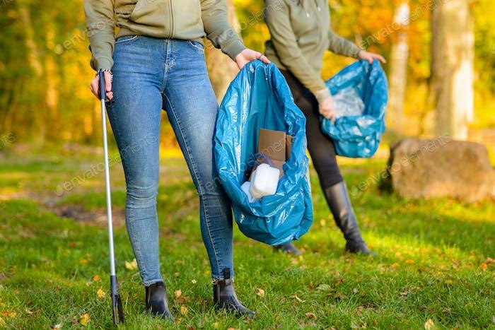 Female volunteers picking up garbage on grass