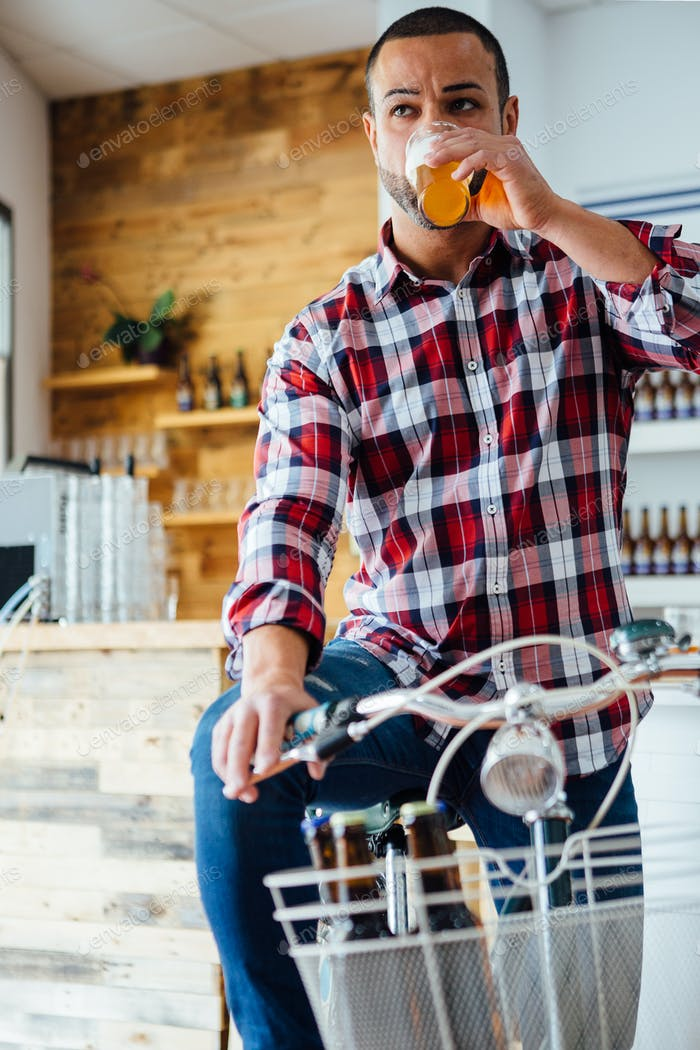 Stylish man drinking beer on bike