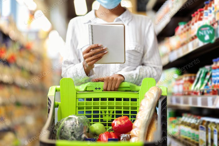 Female Buyer Holding Grocery Shopping Checklist Buying Food In Supermarket