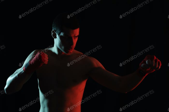 Athletic boxer punching with determination