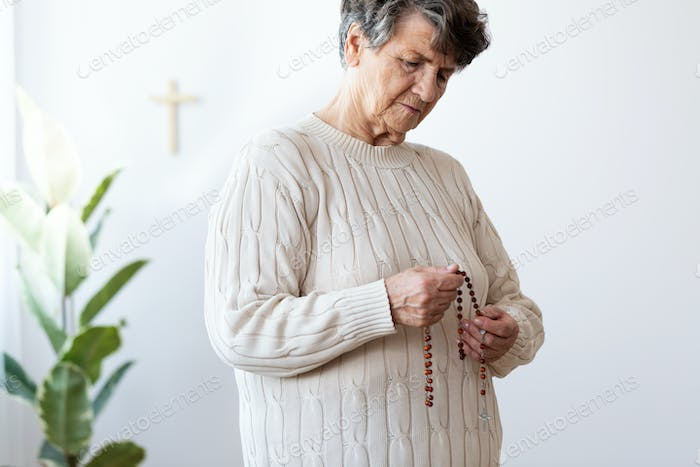Thoughtful catholic elderly woman holding red rosary with a cros