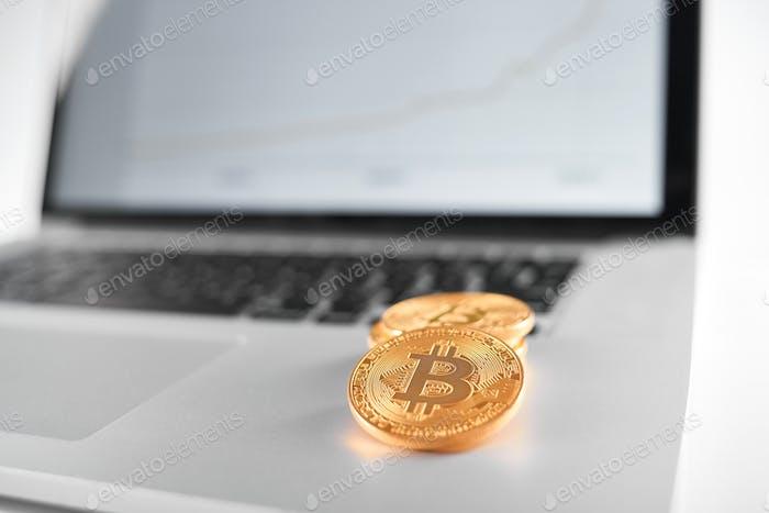 Enfoque nítido en los bitcoins dorados colocados en la computadora portátil plateada con gráfico financiero borroso en su pantalla