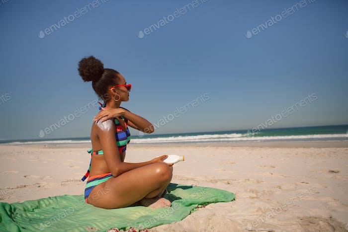 African american woman in bikini applying sunscreen lotion on shoulder at beach