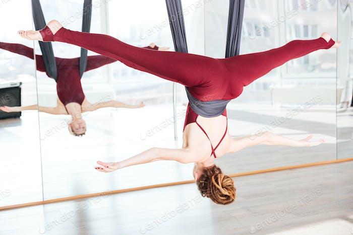 Woman doing pose of antigravity yoga using hammock