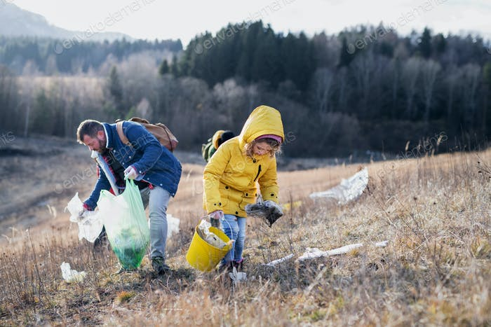 Small child with activists picking up litter in nature, environmental pollution concept