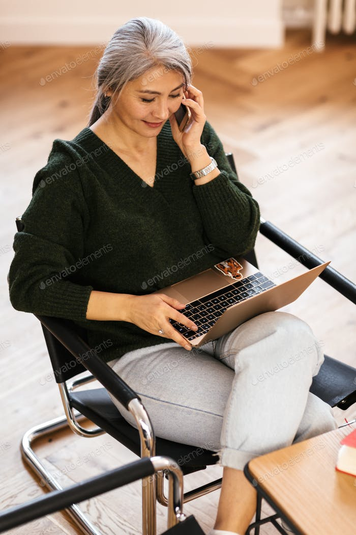 Photo of pleased woman using laptop and talking on cellphone
