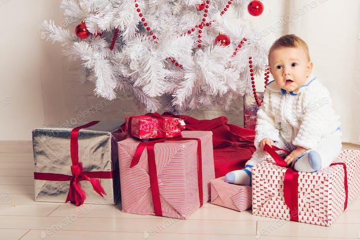 Fröhlicher kleiner Junge spielt in der Nähe des Weihnachtsbaumes