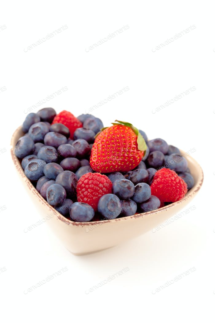 Berries in a heart shaped bowl against a white background