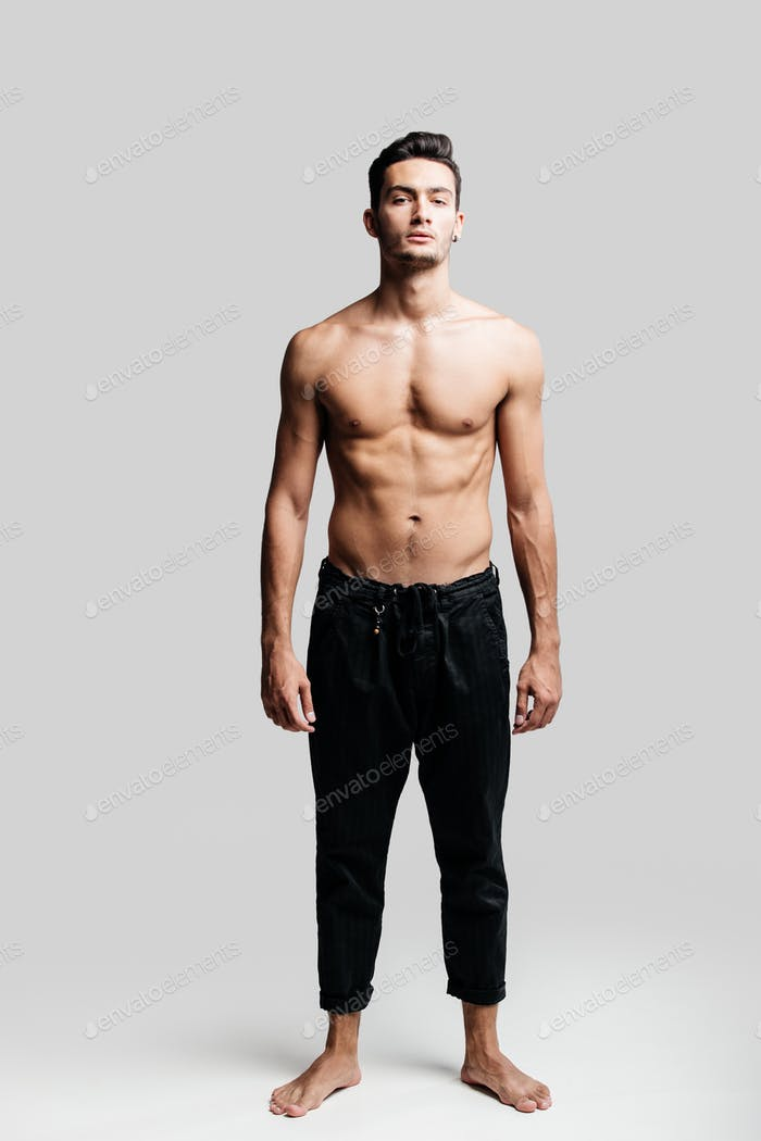 Dark-haired handsome young dancer with bare torso wearing a black sports pants is standing on a