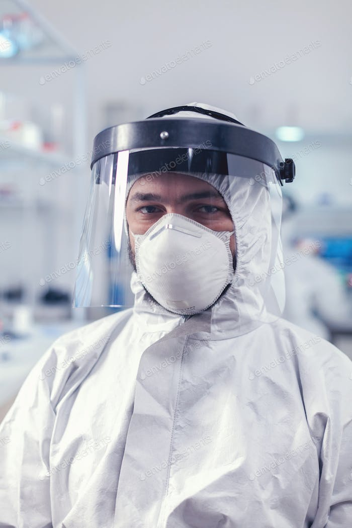 Portrait of medic in research lab looking tired wearing coverall with face shield