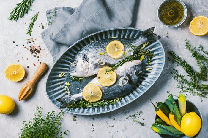 Seafood concept. Cooking dorado or sea bream fish with lemon, herbs, oil, vegetables and spices on