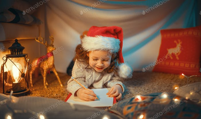girl is writing the letter to Santa
