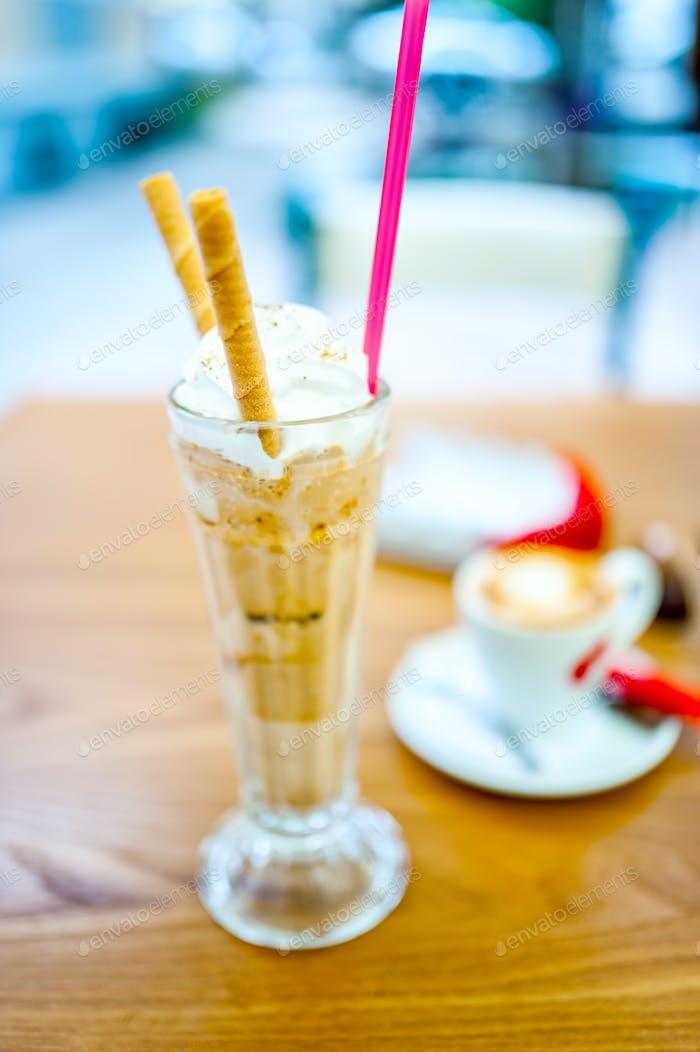 Eiskaffee, Frappe, mit Schlagsahne, Mandelcreme und Keks
