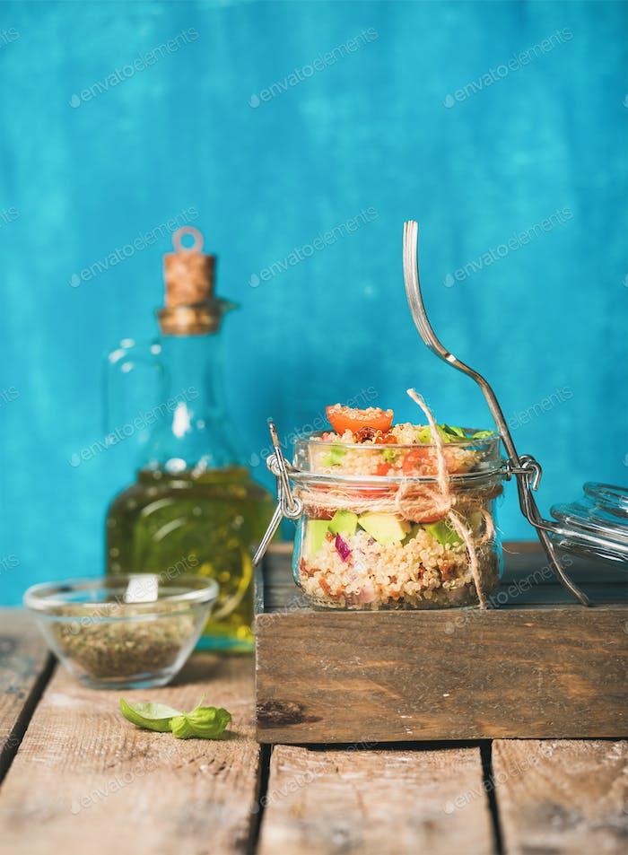 Healthy homemade jar quinoa salad with tomatoes, avocado, fresh basil