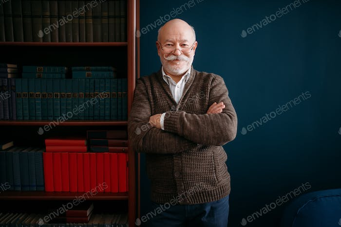 Cheerful elderly man in glasses poses at bookcase