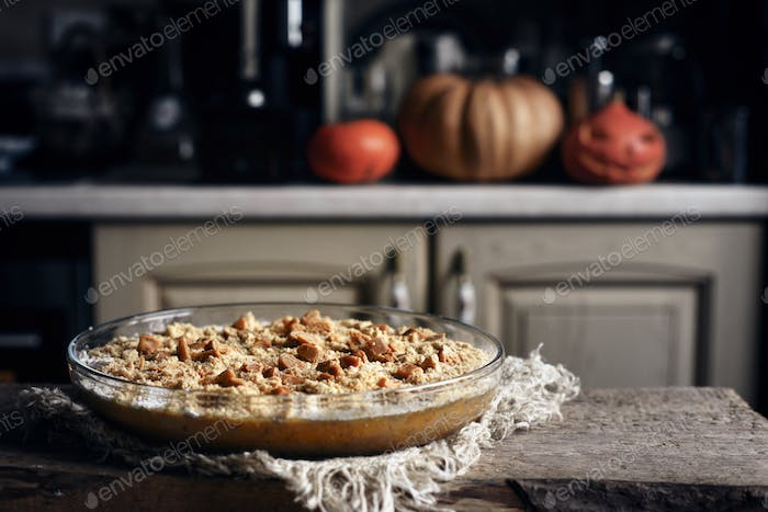 Raw pumpkin dump cake in the baking dish on the wooden table