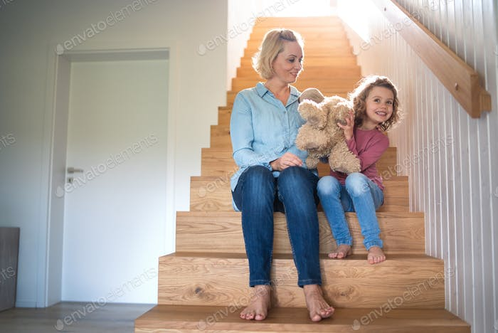 A cute small girl with mother indoors at home, sitting on staircase.