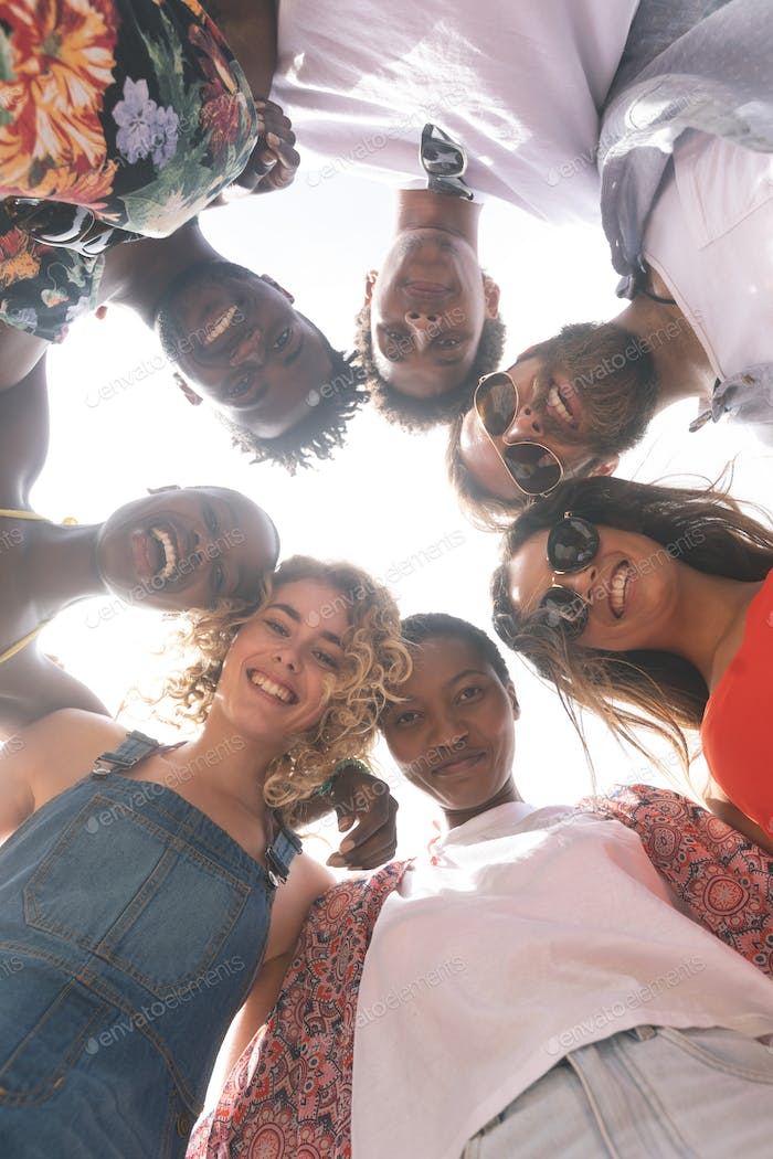 Low angle view of multi ethnic group of friends forming huddle with heads  on beach