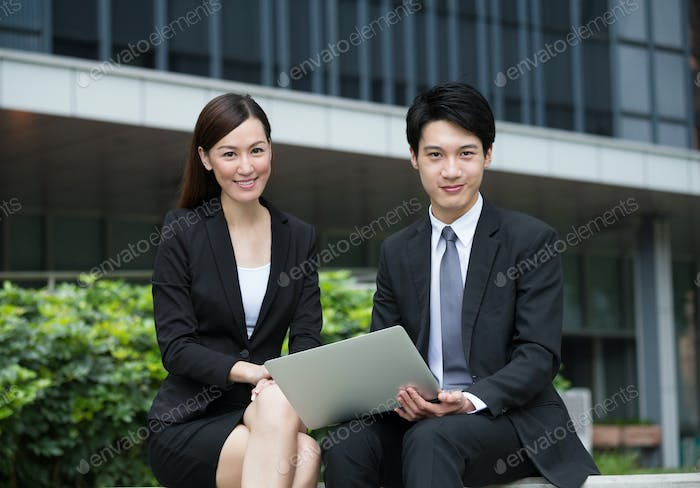 Businesswoman working together with businessman by using laptop computer at outdoor