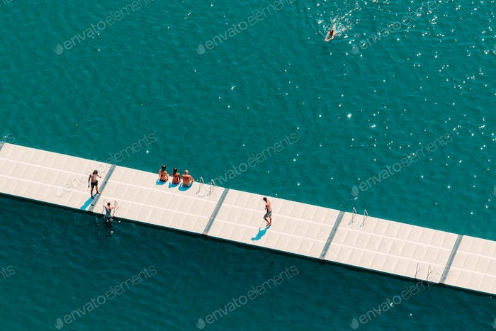 Unrecognizable people enjoying summer afternoon on lake