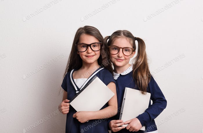 Two small schoolgirls with glasses and uniform standing in a studio, holding notepads