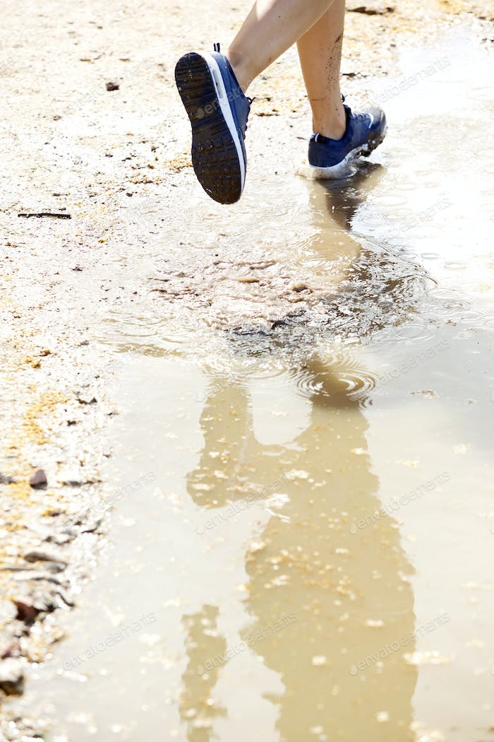 Runner on wet dirt path
