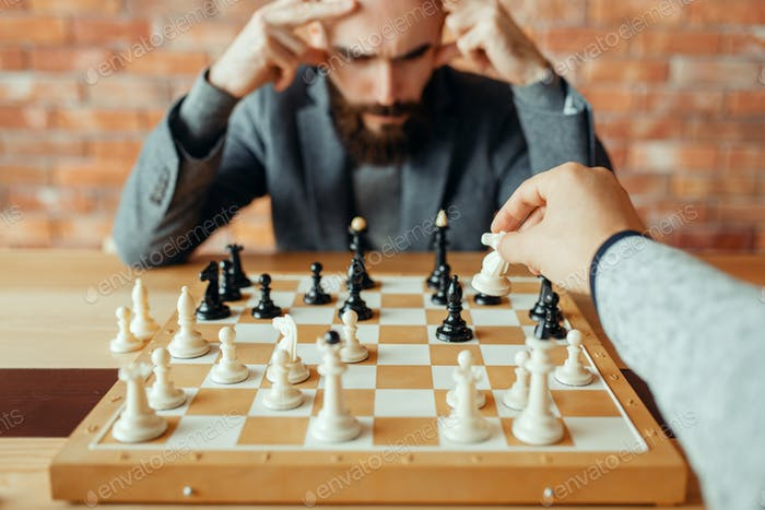 Male chess players playing, white knight move