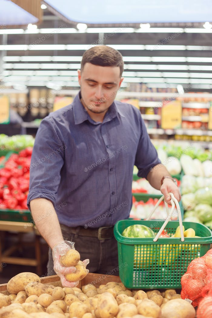 Man takes potatoes at a vegetable market or grocery store. Purchases of vegetables, close-up
