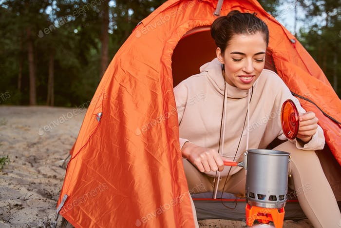 Cheerful female traveler making hot drink during camping