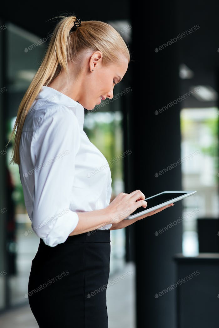 Businesswoman using digital tablet outside of office building