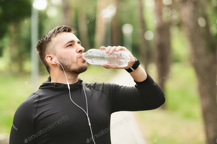 Athletic man drinking water after workout in the park