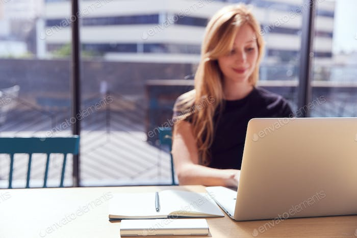 Young Businesswoman At Desk In Modern Office Work Space Using Laptop With Focus On Foreground