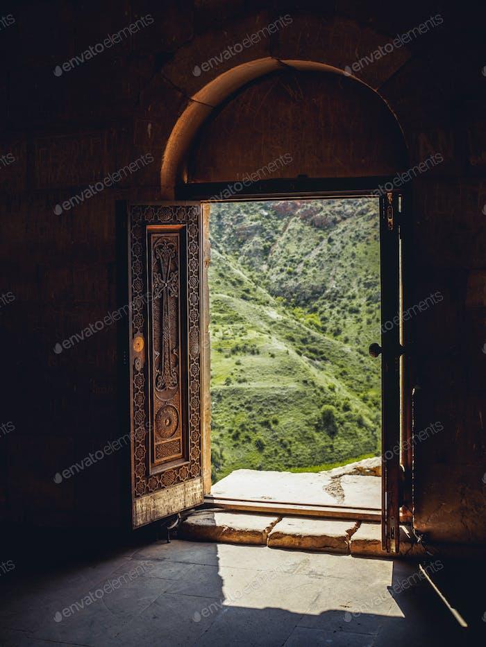 Blick durch Kirchentüren auf grünem Hügel