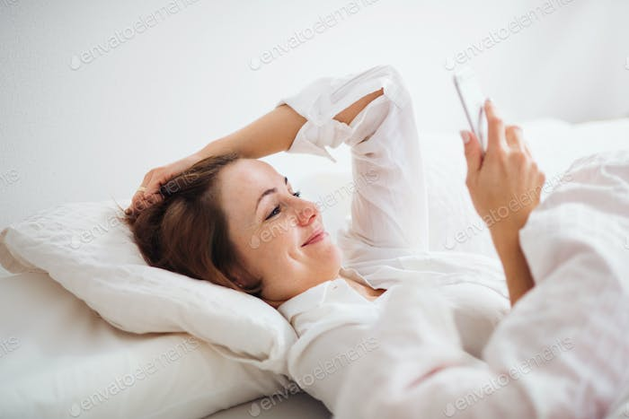 A young woman lying in bed indoors in the morning in a bedroom, using smartphone.
