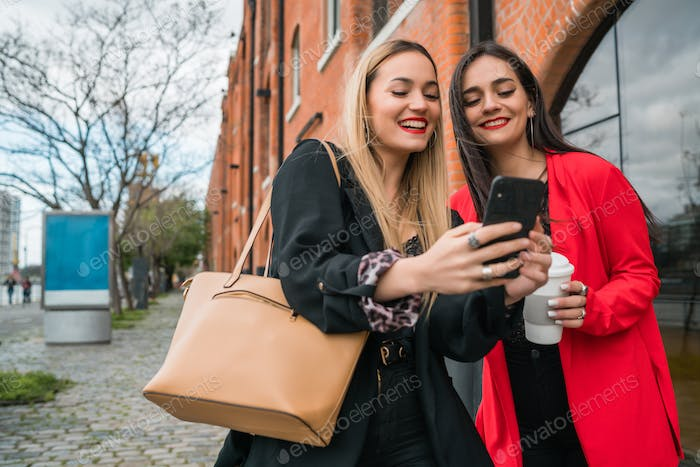 Two young friends using their mobile phone outdoors.