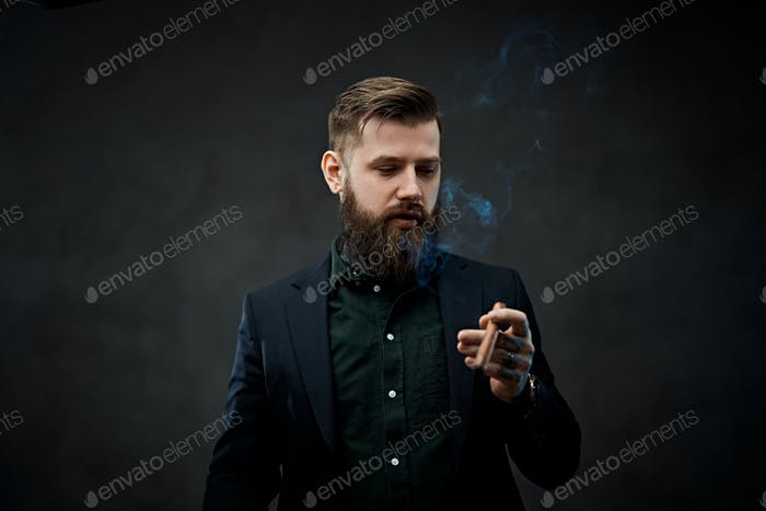 Brutal young businessman smokes a cigar in a dark studio.
