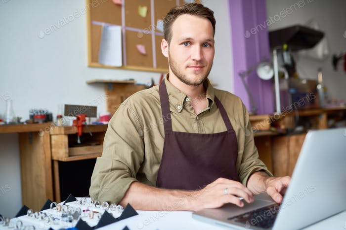 Young Man Using Laptop in Jewelry Workshop