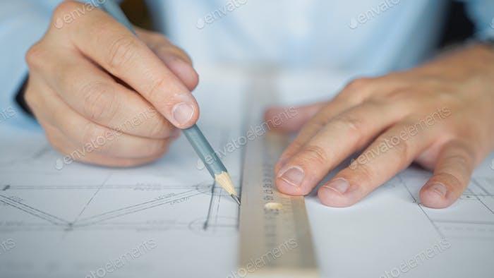 Les mains de l'architecte dessinent un plan de construction