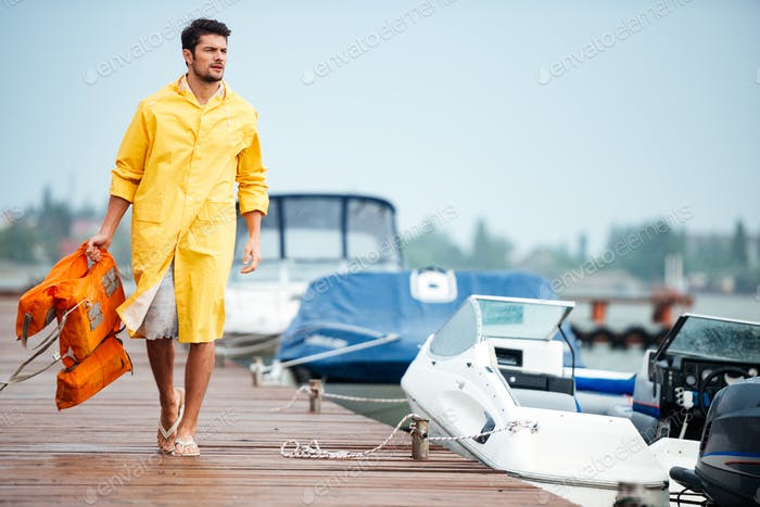 Sailor in yellow cloak at the pier holding life vest