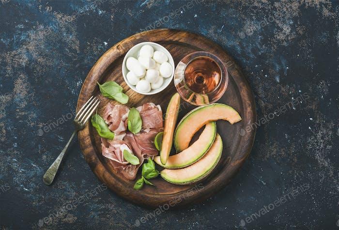 Prosciutto, cantaloupe melon, basil, mozzarella and glass of rose wine