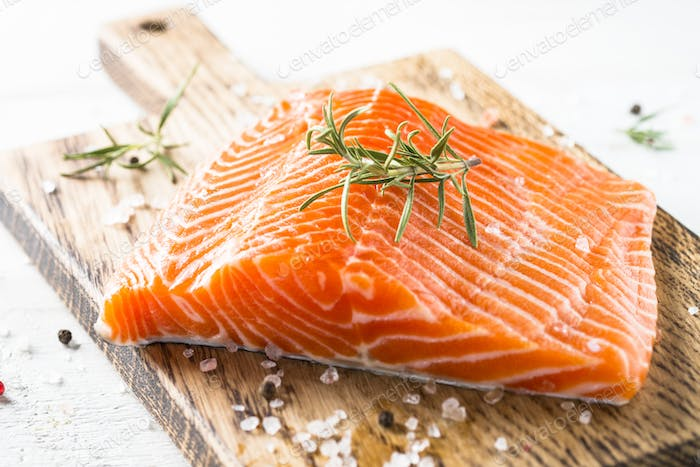 Uncooked salmon fillet with lemon sea salt and rosemary on white
